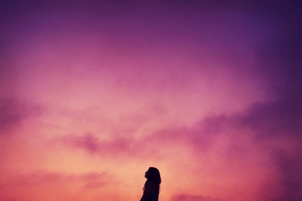 Silhouette of woman against pink sky